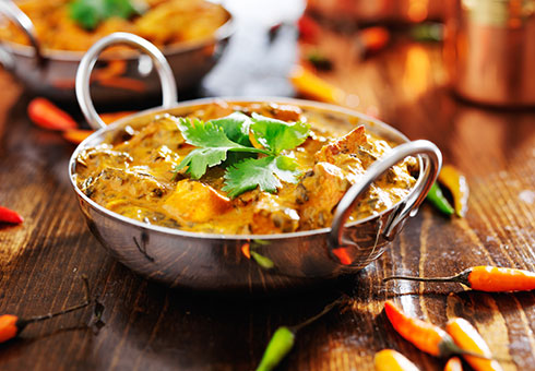 India Chef Macclesfield creamy chicken curry served in a balti dish with fresh chillies
